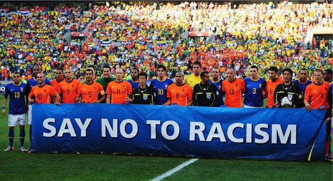 "A soccer team with a ""say no to racism"" banner (c) FIFA"
